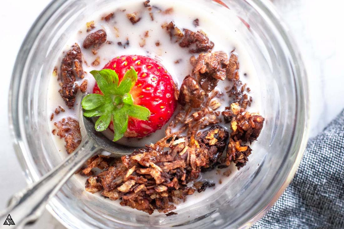 Top view of low carb chocolate granola in a glass topped with strawberry