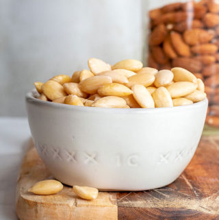 Blanched almonds in a cup with a jar of almonds with skin at the background