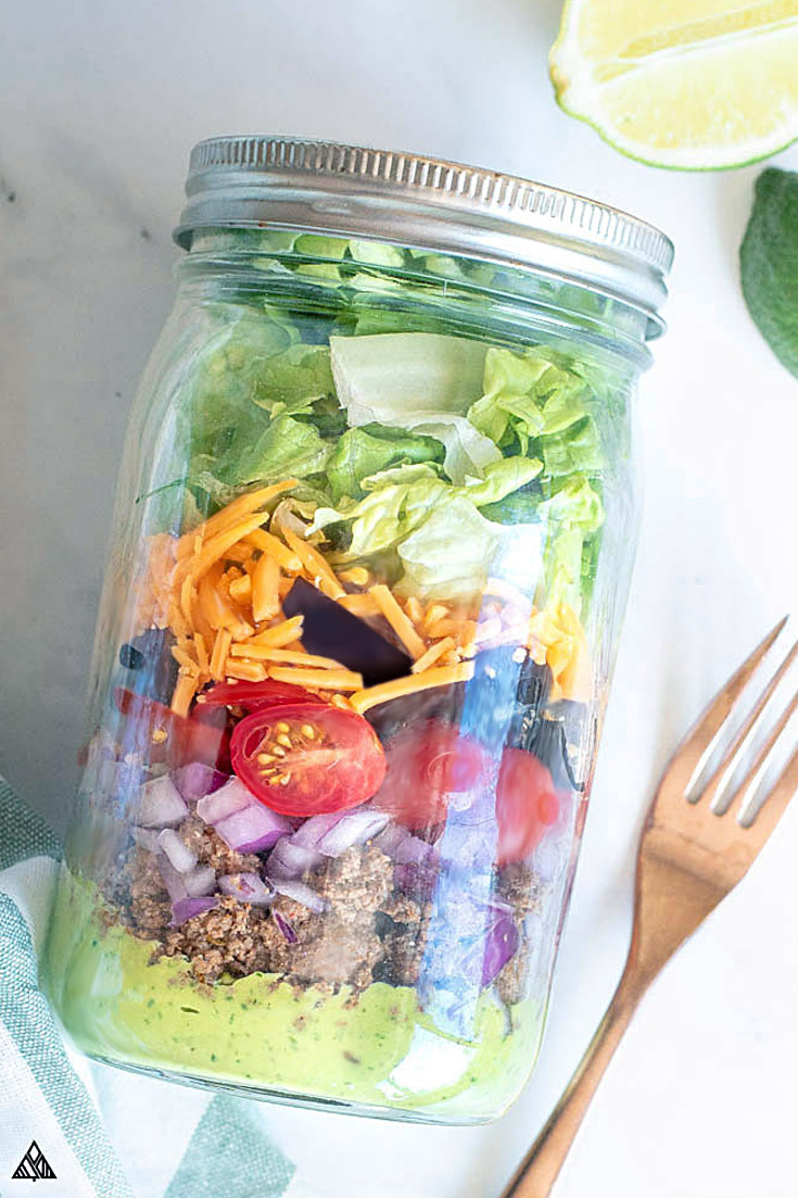Keto taco salad in a jar with wooden fork on the side