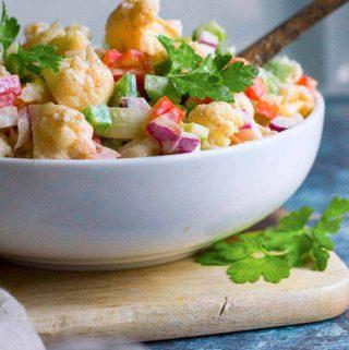 Cauliflower salad in a bowl on top of a cutting board