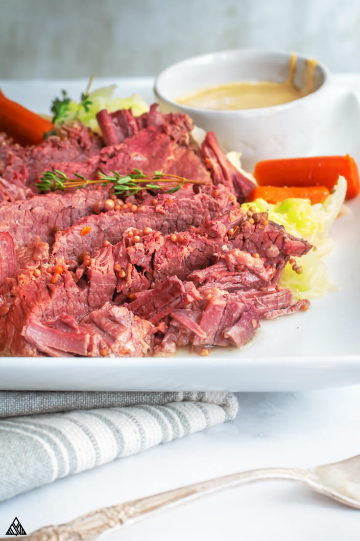 Side view of instant pot corned beef in a white plate