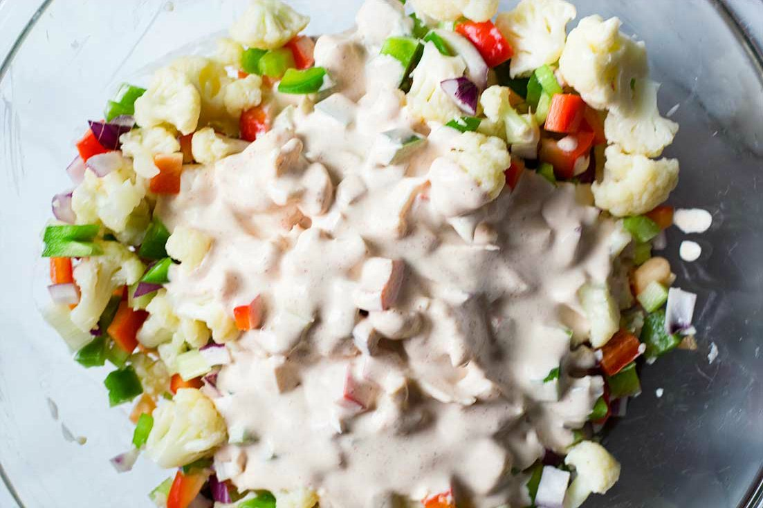 Cauliflower salad ingredients with poured with salad dressing