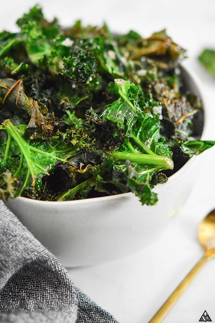 Closer look of kale chips in a white bowl