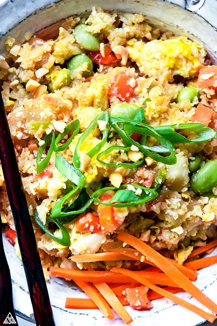Closer look of cauliflower fried rice topped with chopped veggies