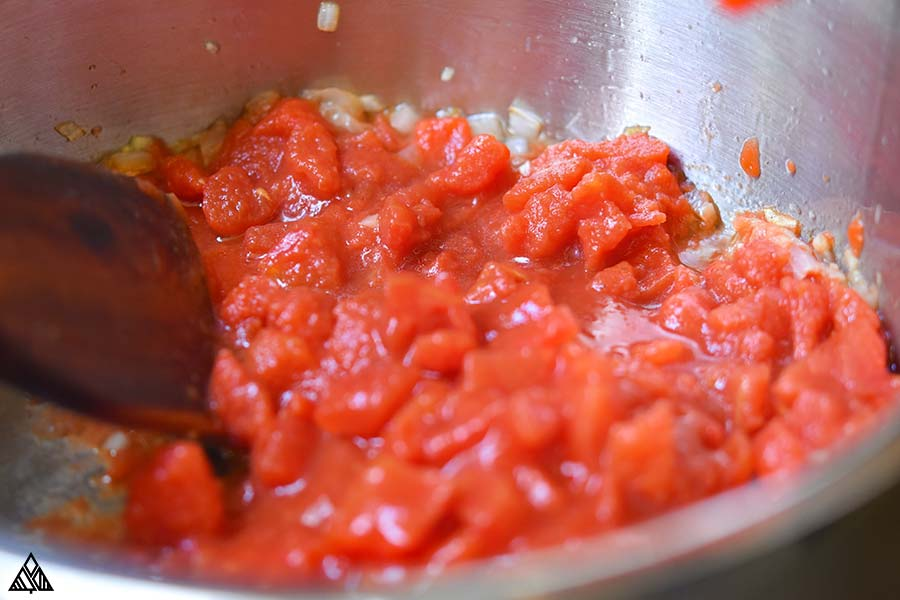 Adding the tomato paste into the sauce pan with the sauted onions