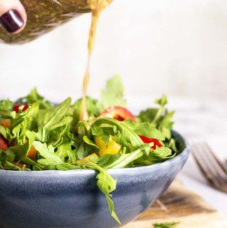 pouring mustard vinaigrette over lettuce