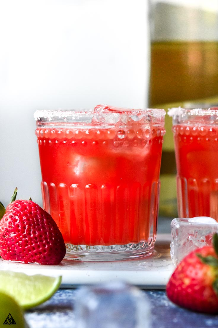 2 glasses of strawberry skinny margarita with strawberries beside the glasses