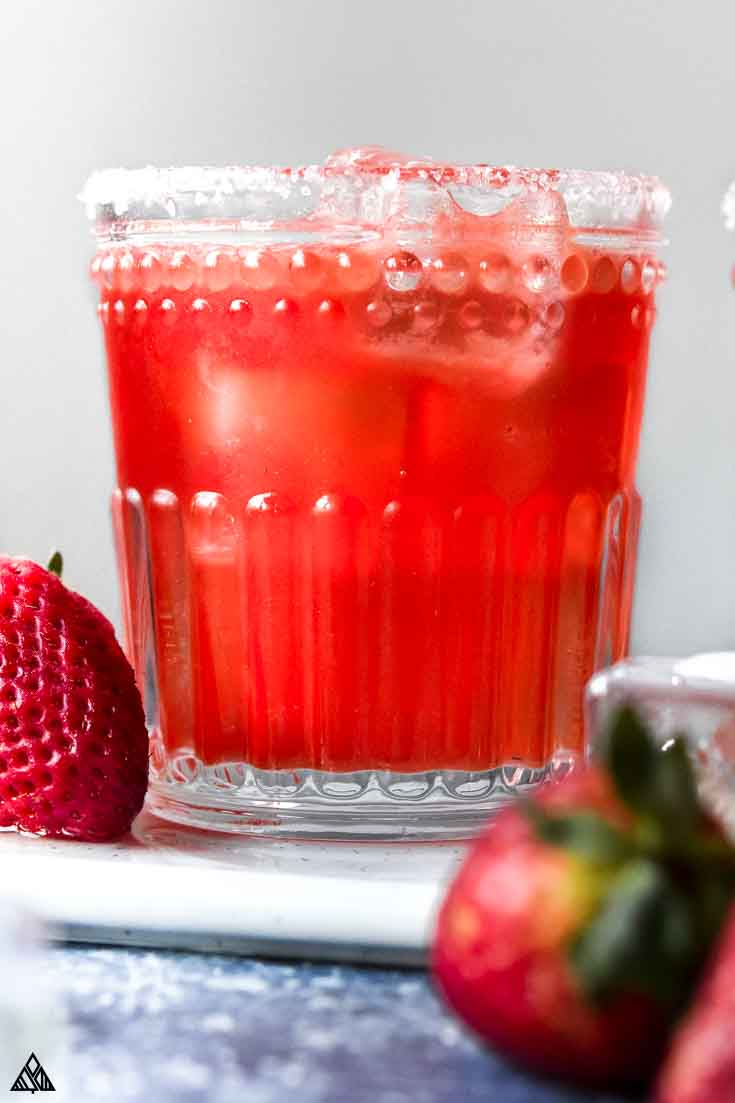 Closer look of strawberry skinny margarita with strawberries on the side
