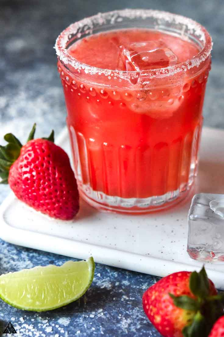 A glass of strawberry skinny margarita with 2 strawberries and a slice of lemon on the side