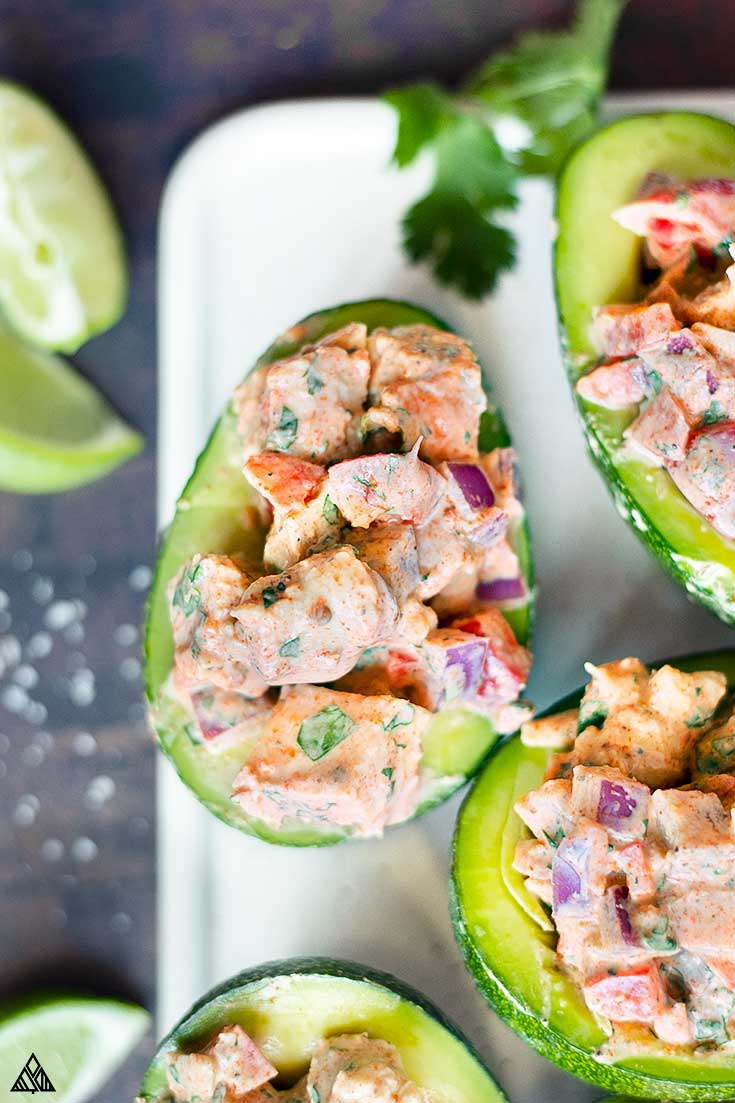 Halved avocado topped with mexican chicken salad
