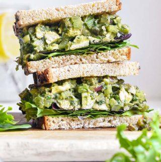 Pile of bread with avocado chicken salad in between each bread