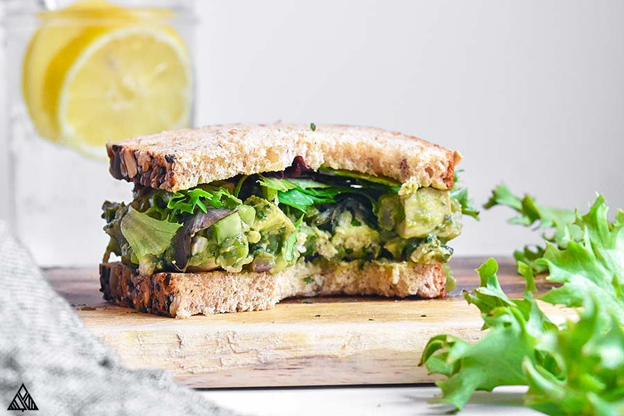 2 slices of bread on a cutting board with avocado chicken salad in between