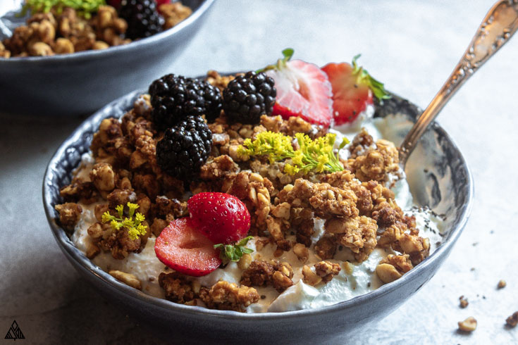 Side view of grain free granola in a bowl with spoon