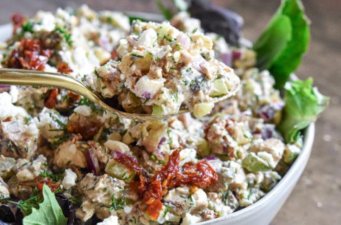 Greek yogurt chicken salad in a spoon with a bowl of greek yogurt chicken salad in the background