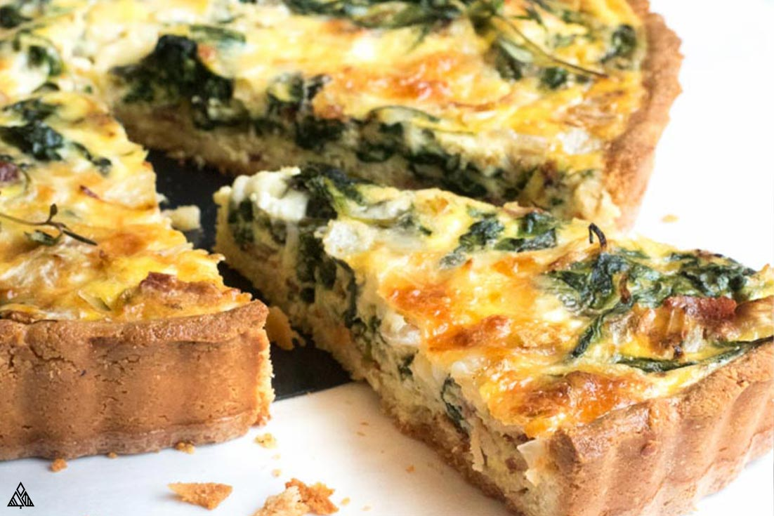 Closer look of sliced spinach quiche