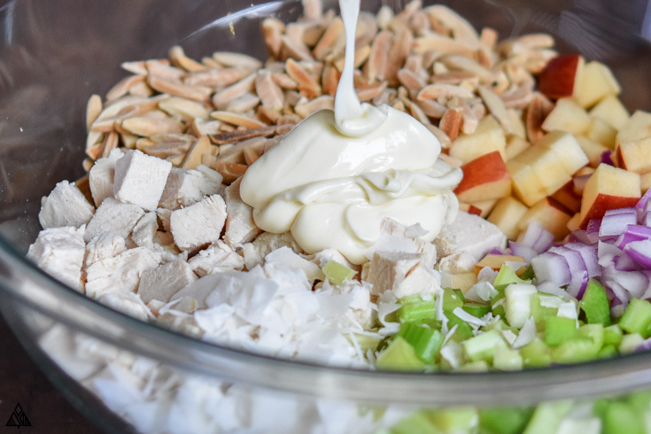Pouring the dressing into the bowl with chicken salad with apples'ingredients