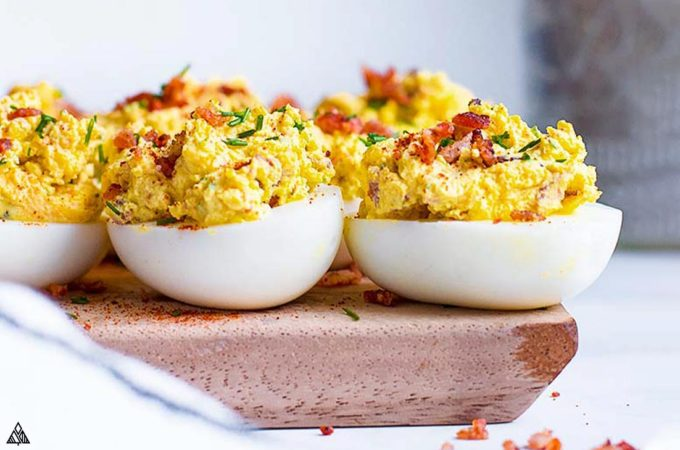 Side view of deviled eggs with bacon on a cutting board