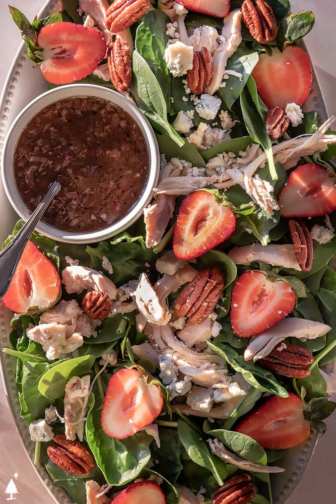 top view of spinach and strawberry salad in a platter