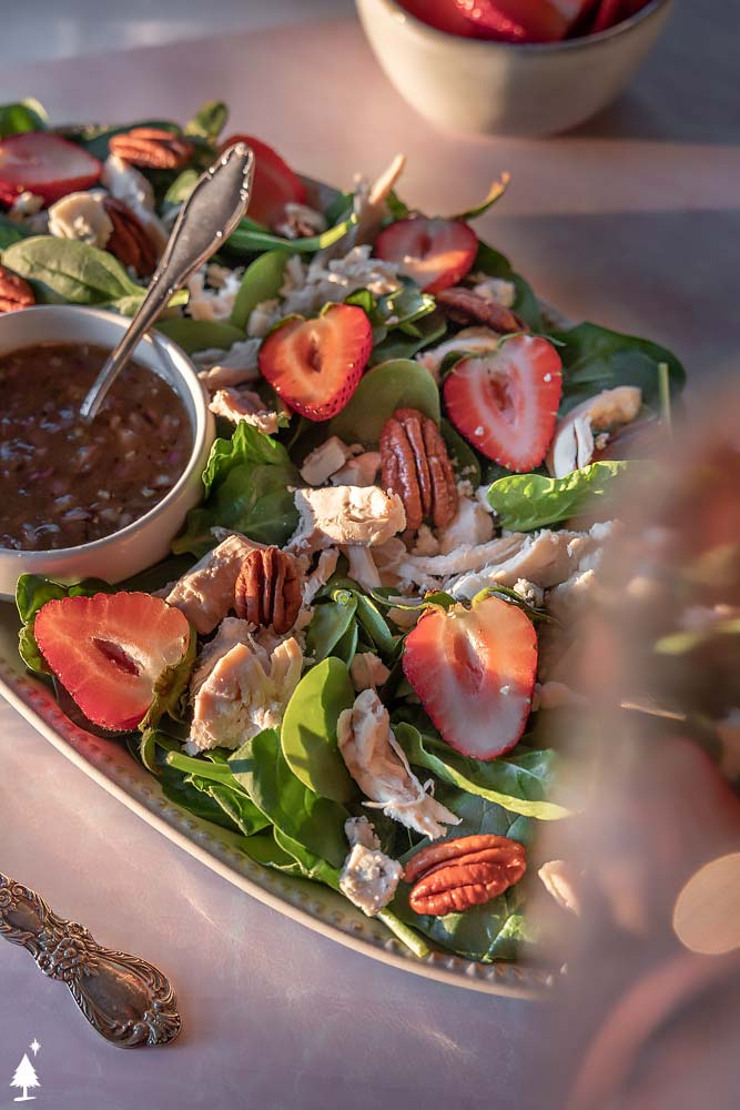 top view of green salad with strawberries in a platter