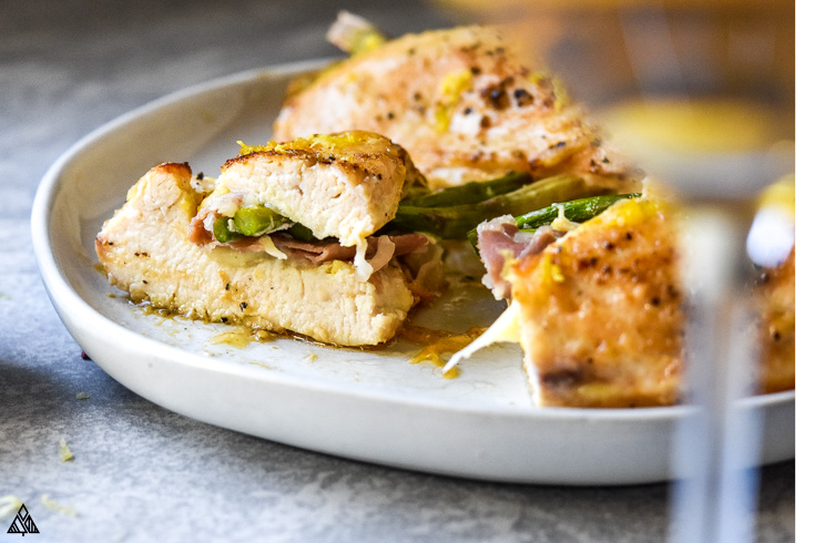Slices of asparagus stuffed chicken in a plate