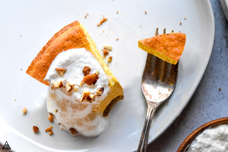 A slice of low carb pumpkin cheesecake in a plate and a fork