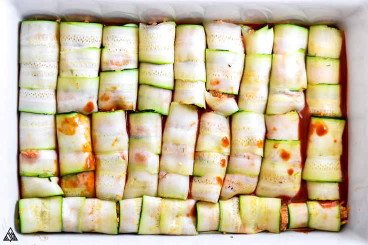Rolled zucchini slices with meat placed into a casserole