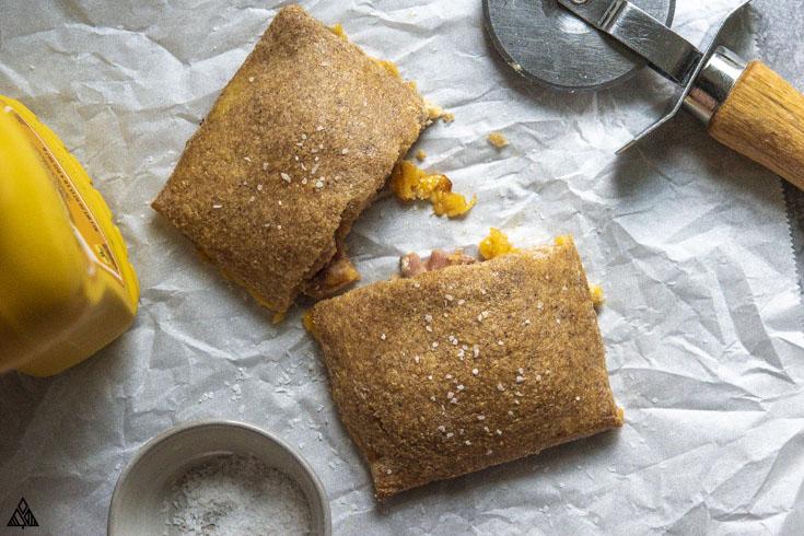 cheesy keto hot pocket being cut in half