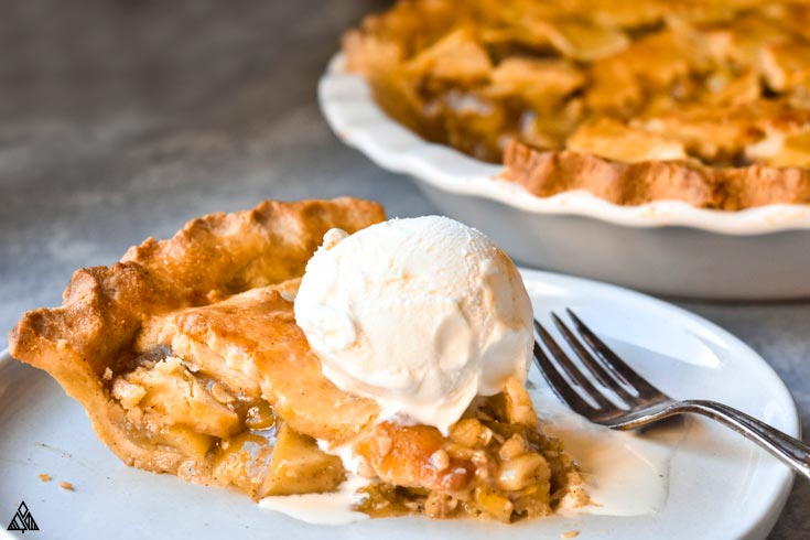 A slice of low carb apple pie in a plate with a scoop of ice cream on top