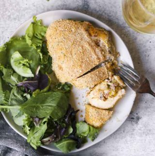 cream cheese stuffed chicken in a plate with fork