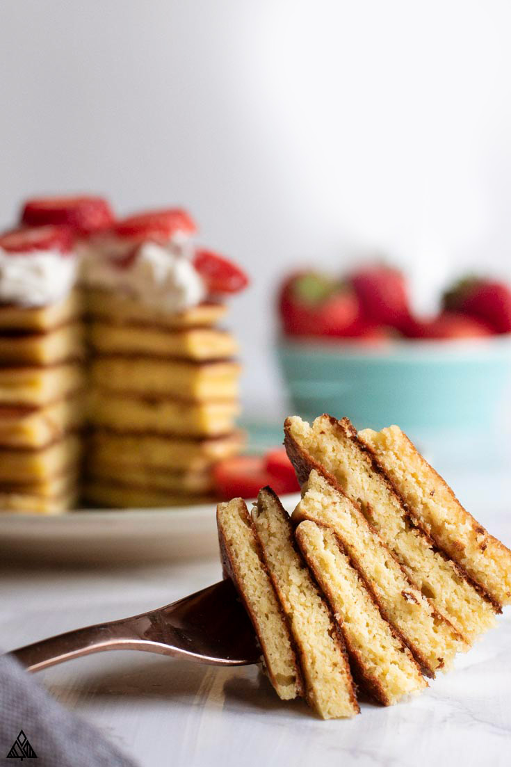 Slices of almond flour pancakes stack in a fork and a plate full of almond flour pancakes in the background