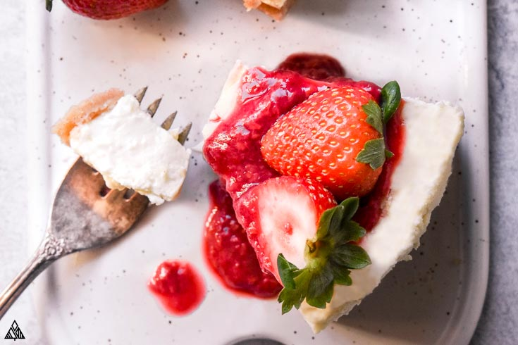 Slice of low carb cheesecake with strawberries on top