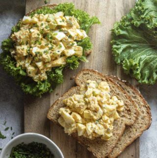 Classic egg salad recipe in a sandwich slice on top of a cutting board