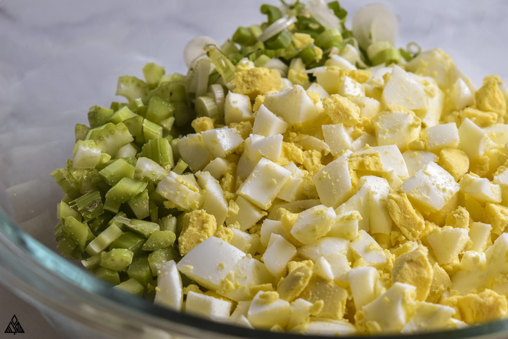 All the ingredients for deviled eggs salad in a bowl