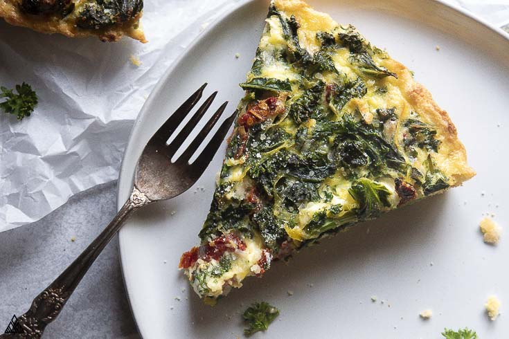 A slice of kale quiche in a plate with a fork