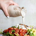 Pouring the homemade ranch dressing into a salad