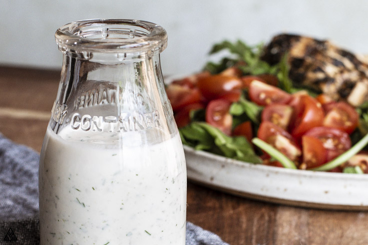Closer look of homemade ranch dressing on a jar and a plate of salad on the background