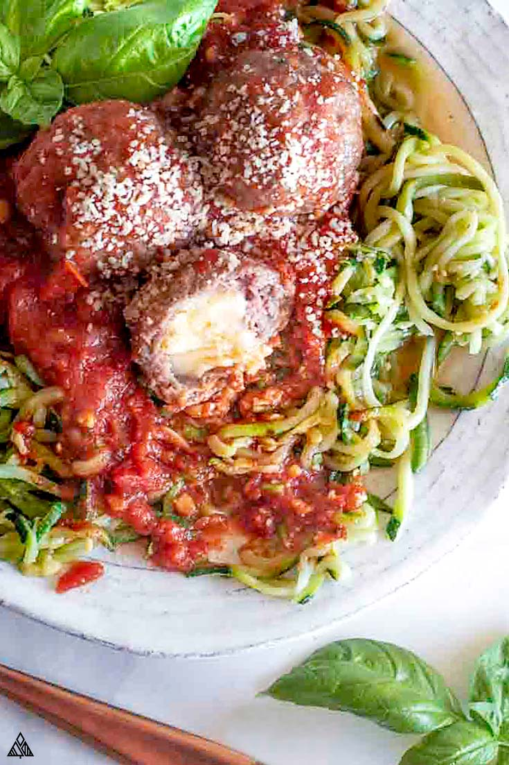 mozzarella stuffed meatballs on a bed of pasta