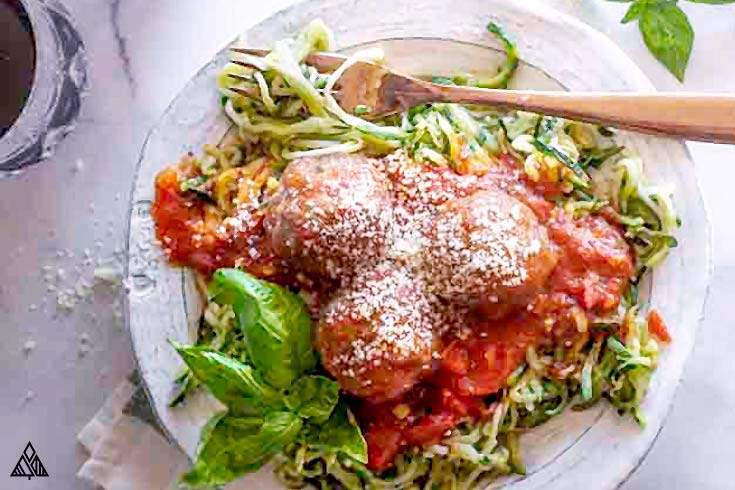 low carb mozzarella stuffed meatballs on a bed of zucchini noodles
