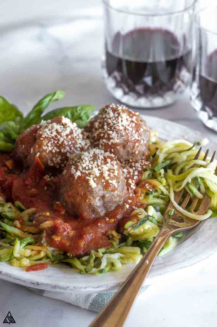 Closer look of mozzarella stuffed meatballs in a plate with veggies