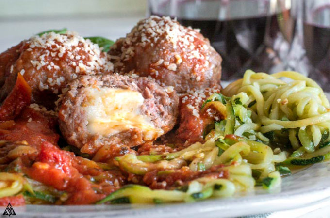 Side view of mozzarella stuffed meatballs in plate with a piece slightly bitten
