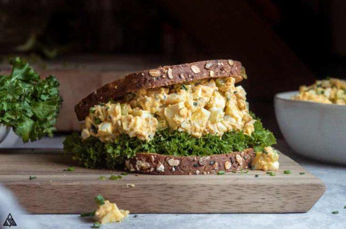 egg salad sandwich on a cutting board