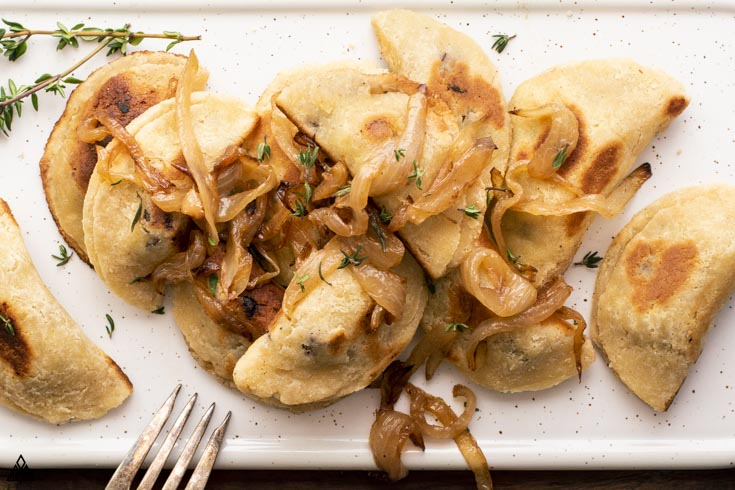 low carb dumplings on a platter with onions