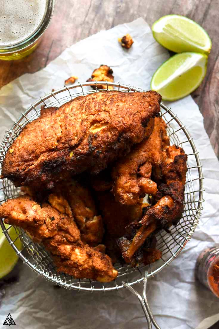 basket full of low carb fried chicken with limes and hot sauce