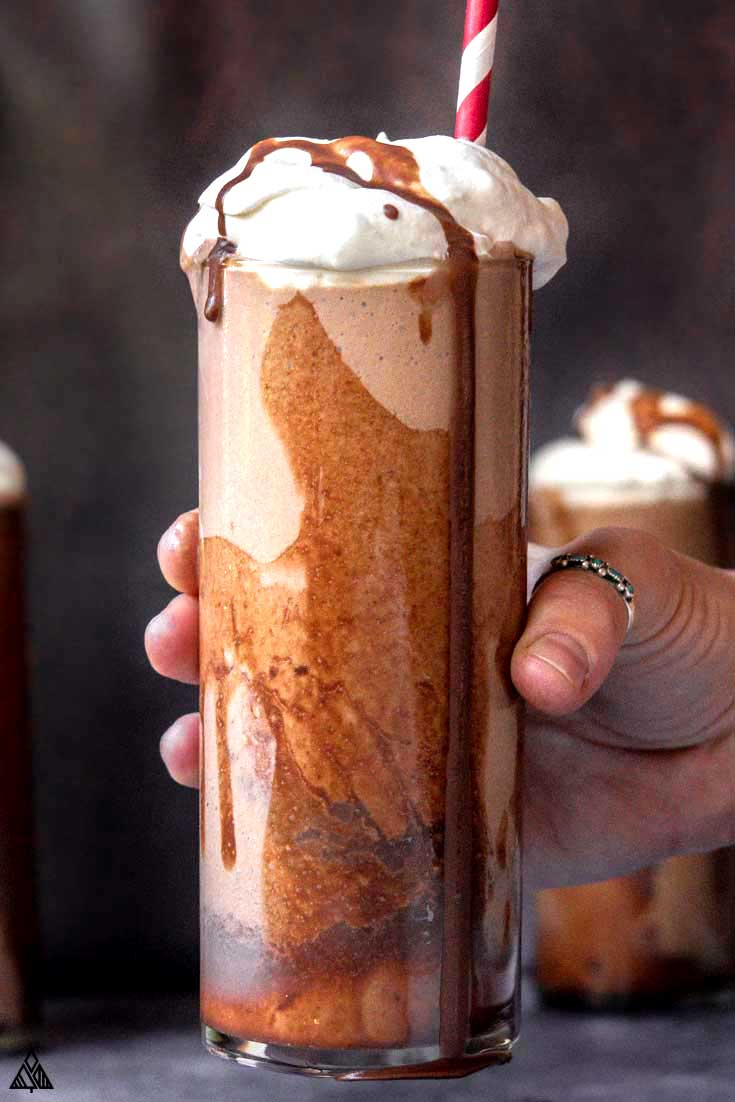 glass of low carb milkshake with whipped cream and chocolate syrup