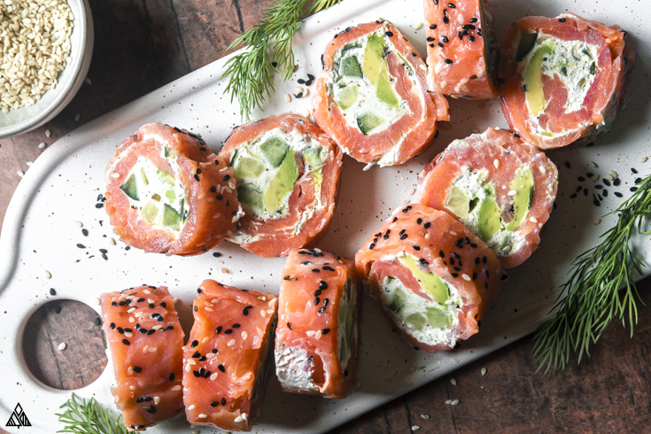 Slices of smoked salmon roll ups on a cutting board