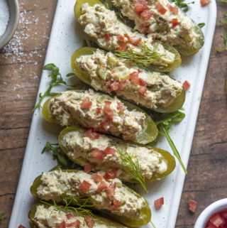 Tuna salad pickle boats laid on a cutting board