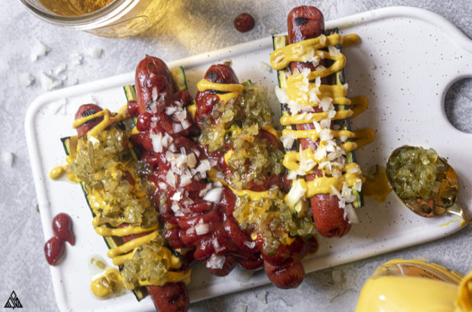 Top view of zucchini hotdogs with toppings