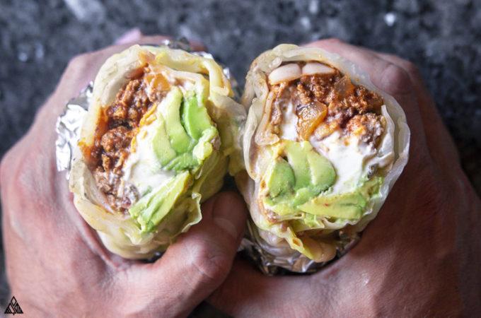 Hand holding 2 sliced low carb burritos