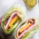 close up shot of turkey club wraps on a plate