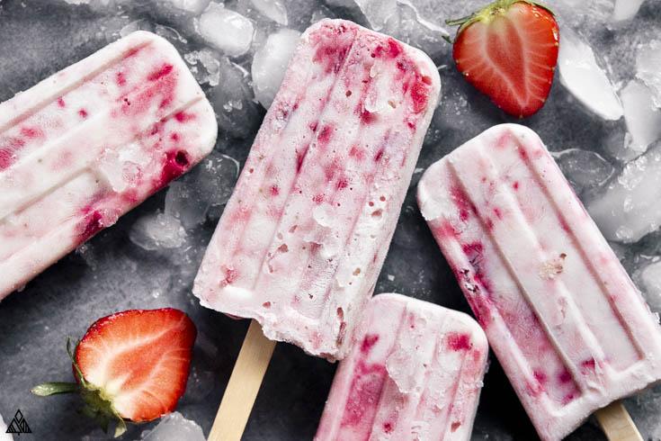 close up shot of yogurt popsicles with fresh strawberries